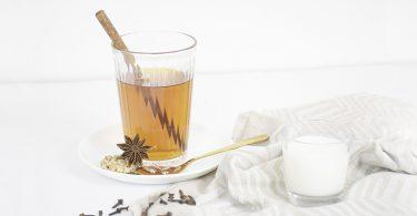 Chai in einem Glas mit Zuckerstange, daneben ein kleines Glas Milch, dekoriert mit Gewürzen