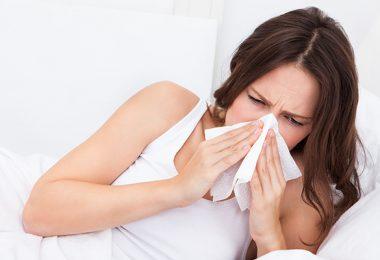 Frau liegt im Bett und niest
