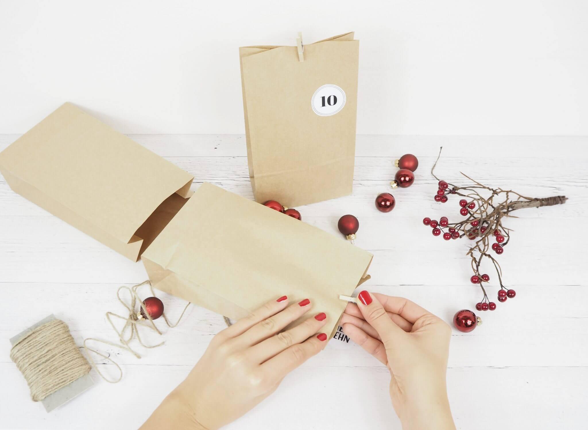 Papiertüten für den Adventskalender werden befüllt und verschlossen
