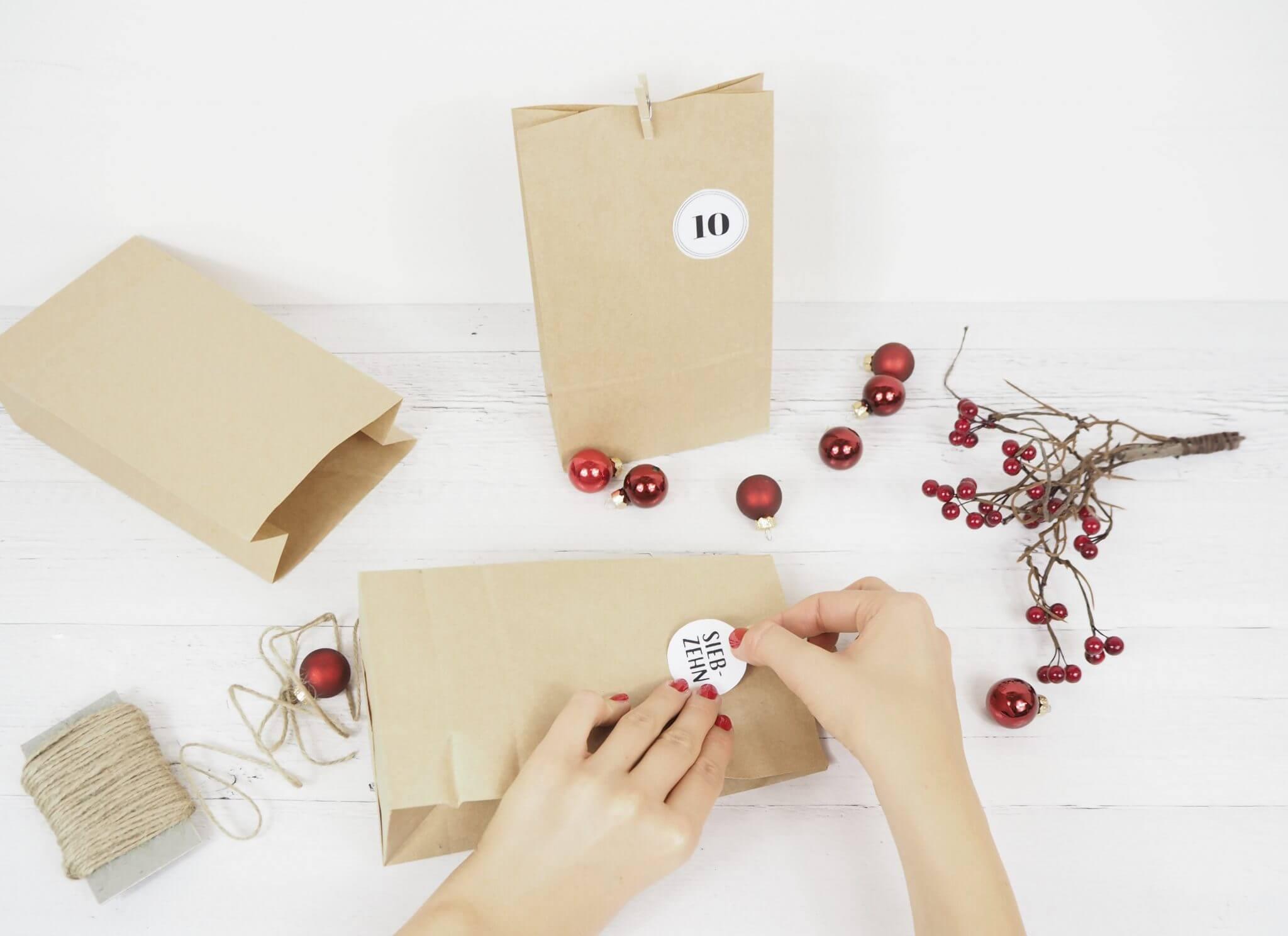 Hand die Zahlen auf Adventskalendertürchen klebt