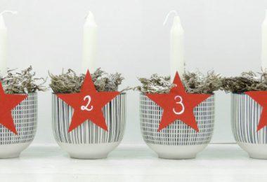 Kerzen in Tassen, durchnummeriert von 1-4 auf roten Sternen und gefüllt mit Moos