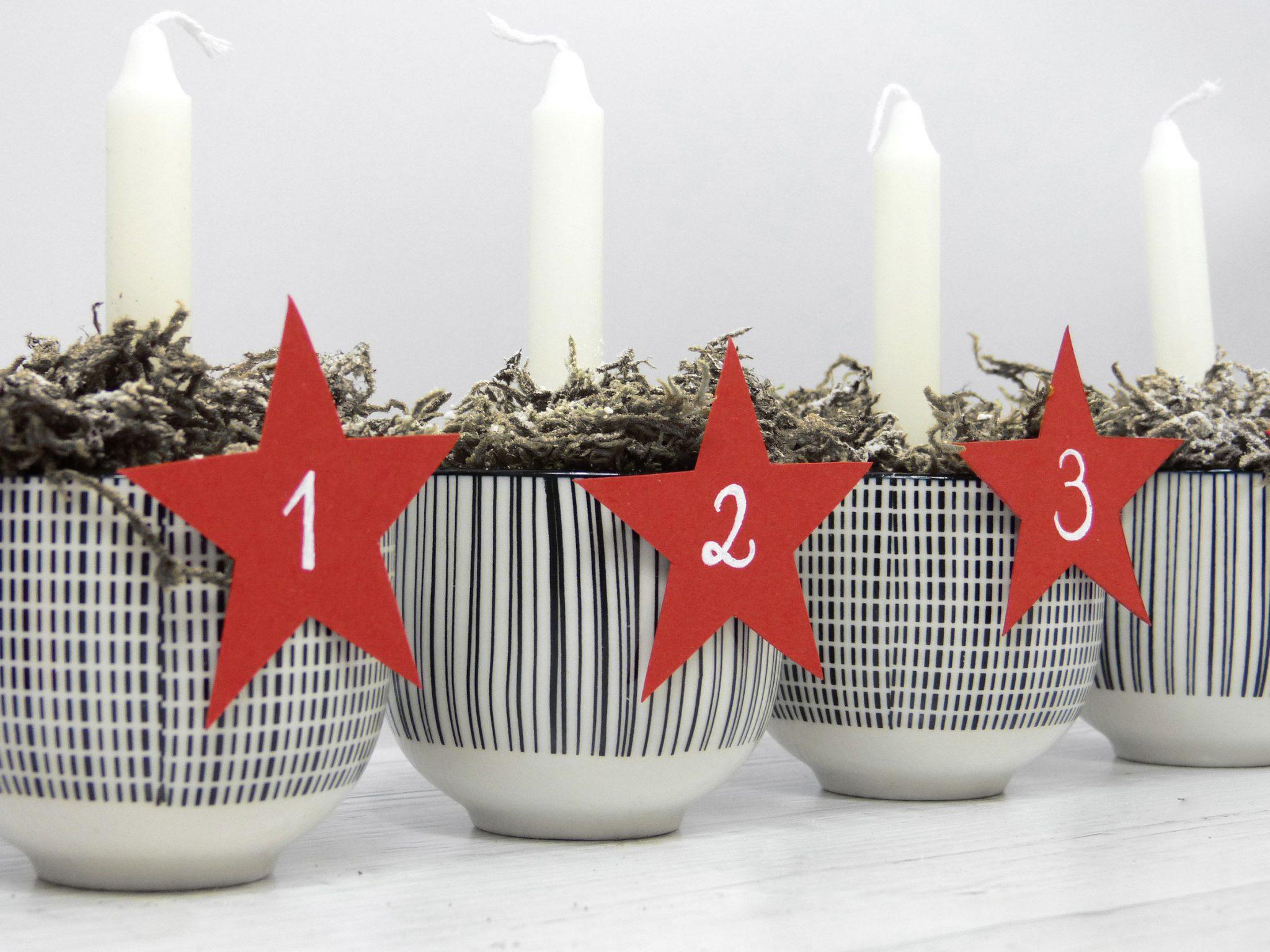 Drei Tassen mit aufgeklebten Papiersternen und weißen Christbaumkerzen, gefüllt mit Moos