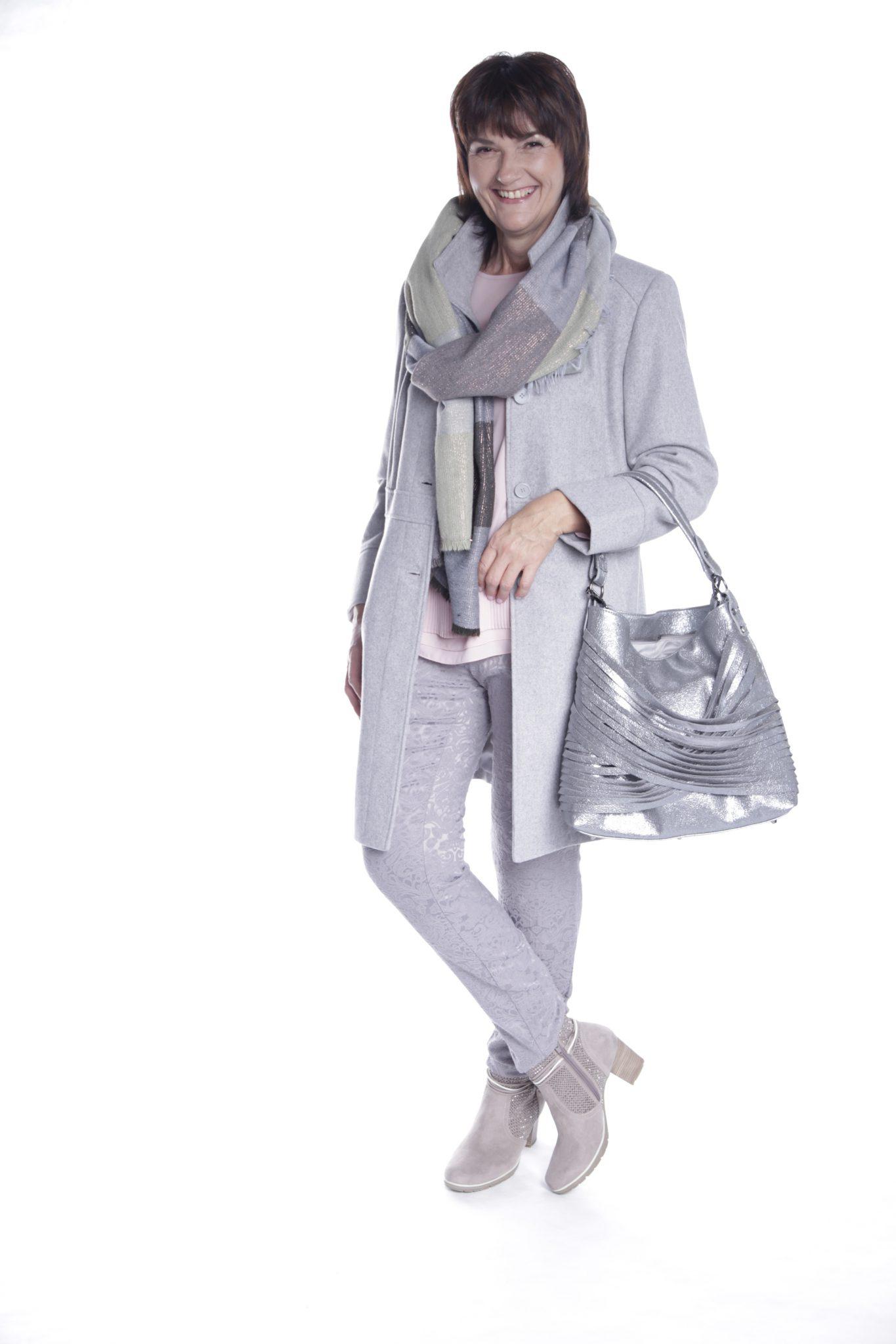 Frau in grauem Outfit mit Hose, Mantel, Schal