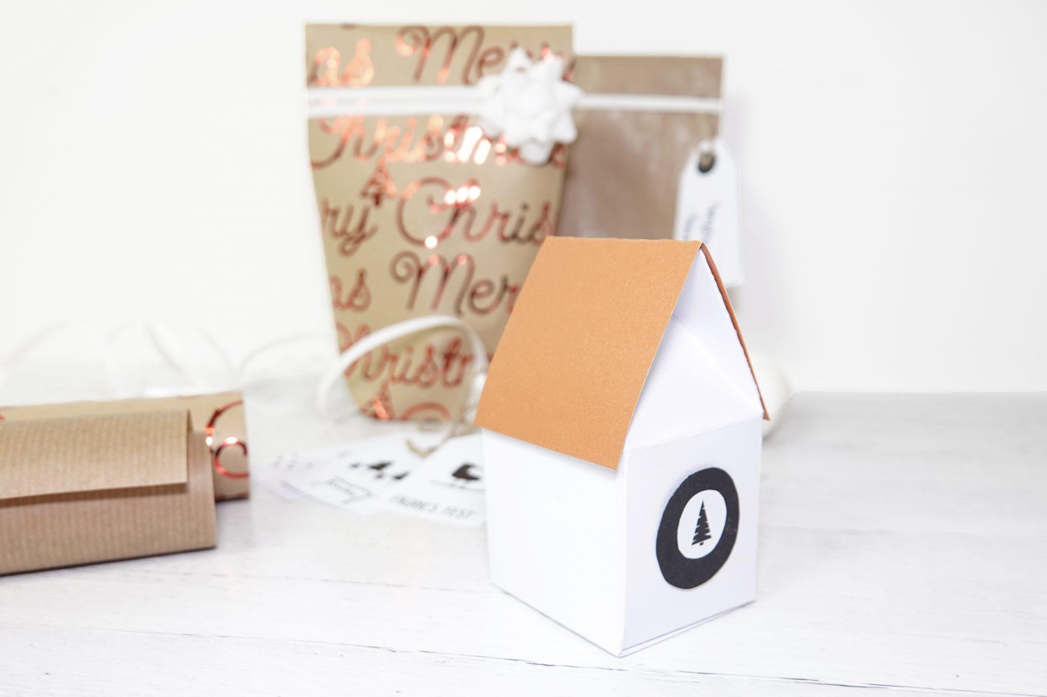 Detailaufnahme der Häuschenverpackung mit hellbraunem Dach und schwarzem Sticker