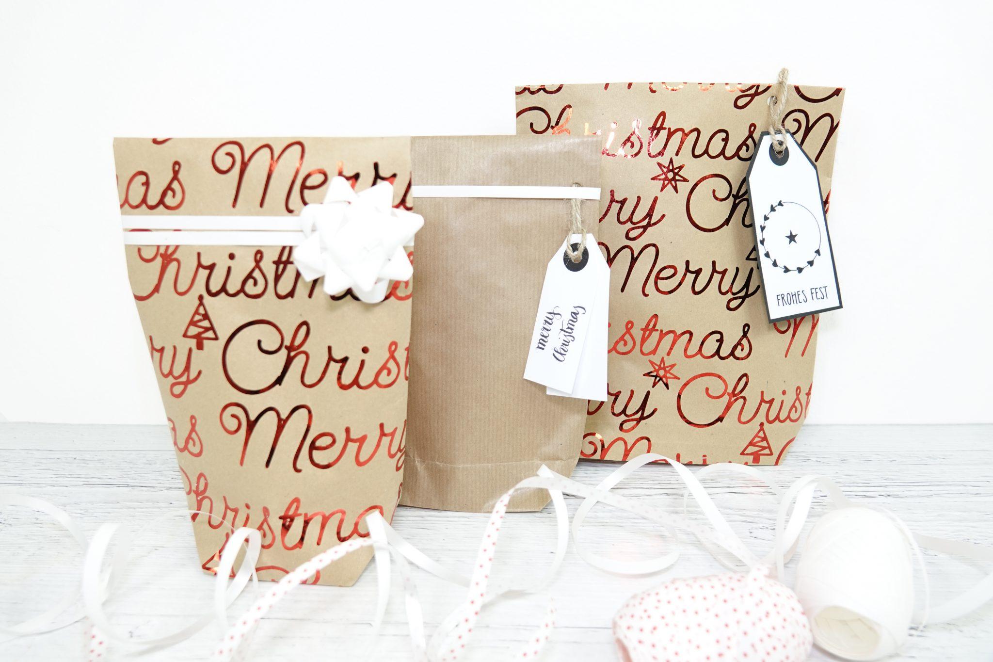 Detailaufnahme der Geschenktüten aus Packpapier und braunem Geschenkpapier mit rotem Merry-Christmas-Schriftzug