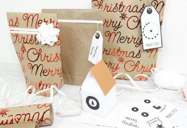 Geschenktüten mit Merry-Christmas-Schriftzug, davor ein Haus gebastelt aus Tonpapier und Geschenkbänder sowie Geschenkanhänger