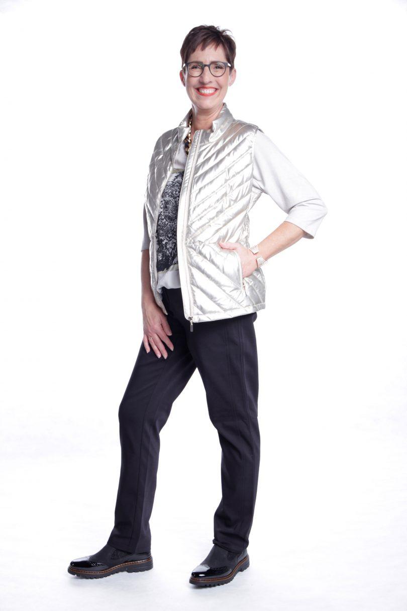 Frau präsentiert Outfit mit weißer Steppweste