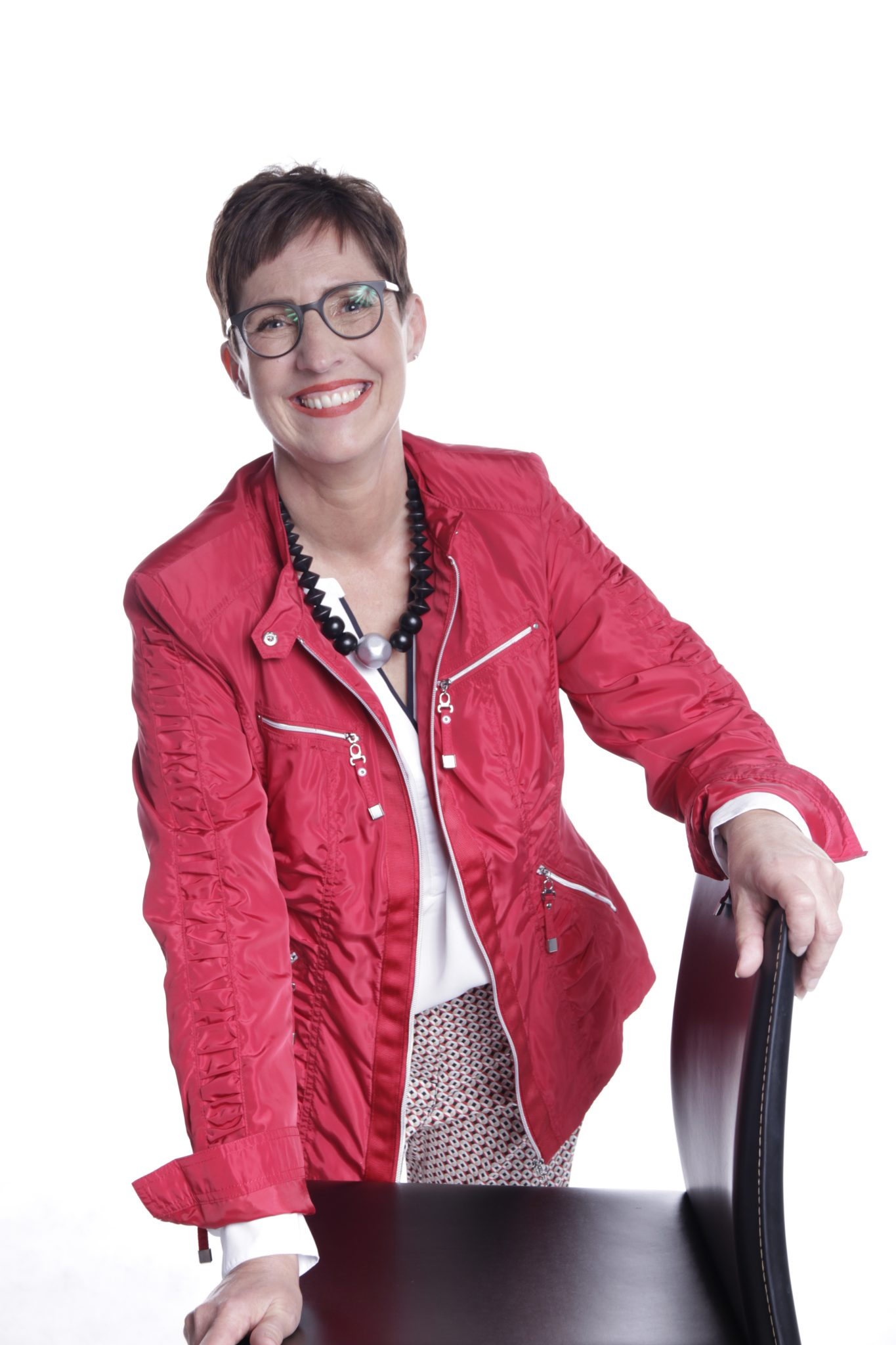 Frau post mit Stuhl in roter Jacke