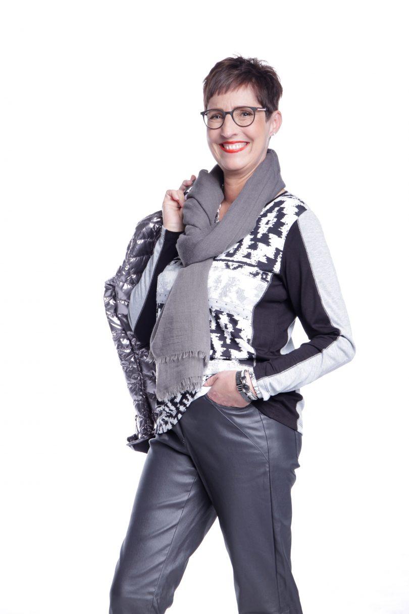 Frau posiert mit Jacke über Schulter