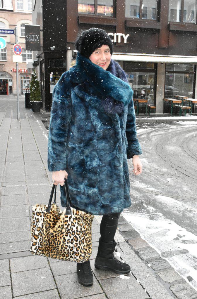 Stilheldin Susanne beweist mit ihrem blauen Pelzmantel und der Leo-Print Tasche Stilsicherheit