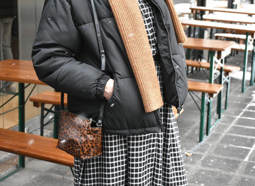 Zur schwarzen Daunenjacke kombiniert Helga-Maria eine kleine Schultertasche im angesagten Leo-Print.