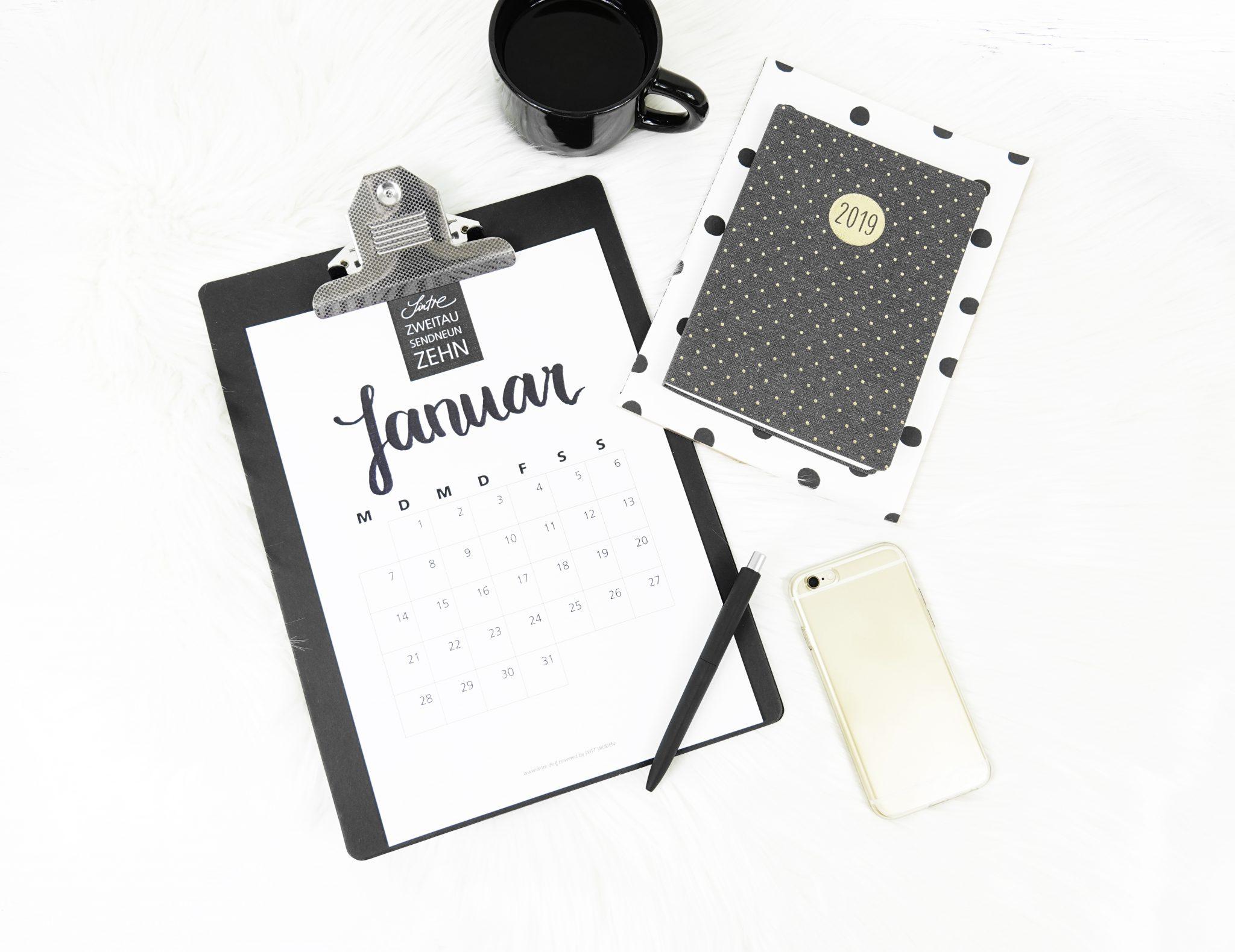 Klemmbrett von oben mit Kalender, Stift, Handy und Kaffeetasse