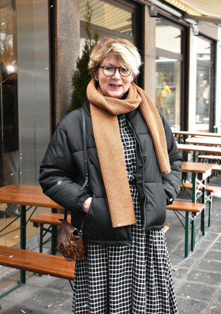 Helga-Maria liegt mit ihrer schwarzen Daunenjacke, dem karierten Kleid und dem camel-farbenen Schal voll im Jacken Trend.