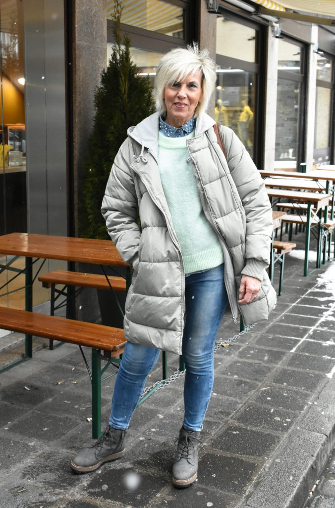 Jacken Trends: Stilheldin Renate setzt auf einen grauen Daunenmantel zum lässigen Outfit.