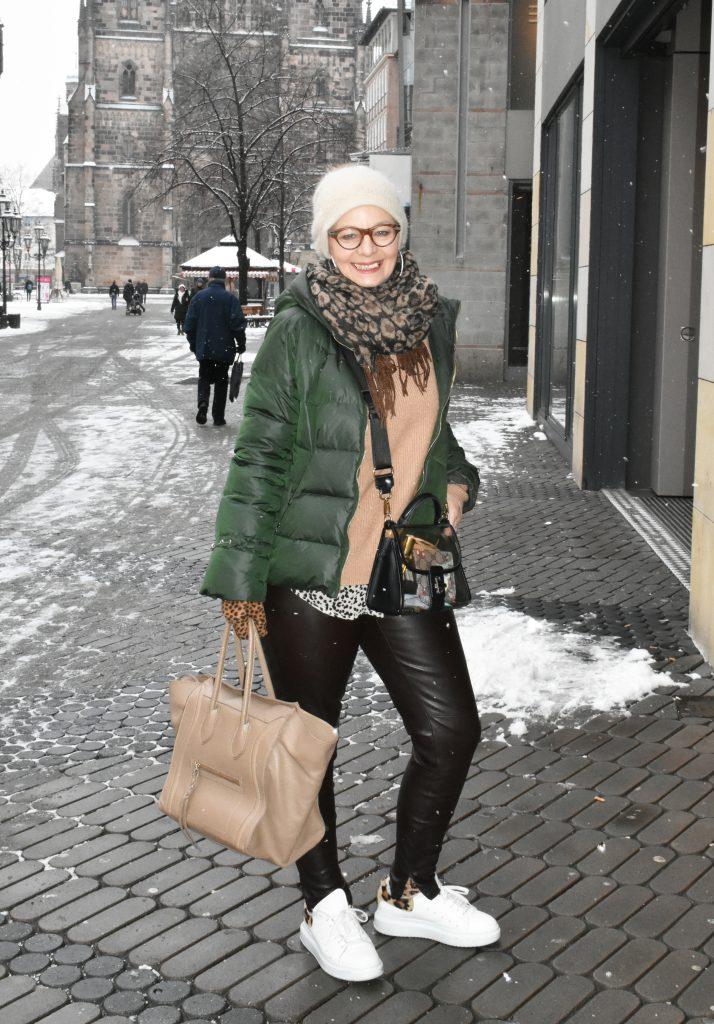 Stilheldin Antje kombiniert ihre grüne Daunenjacke mit einem Camel-farbenen Pullover und Accessoires im Leo-Print