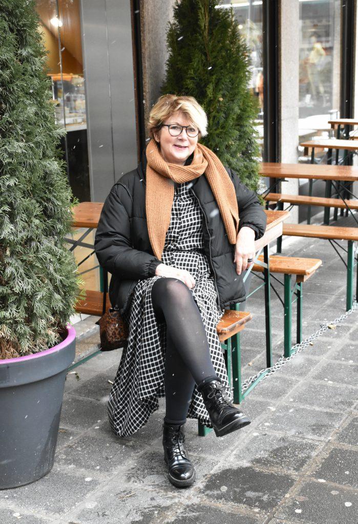 Stilheldin Helga-Maria in einer schwarzen Daunenjacke und kariertem Kleid