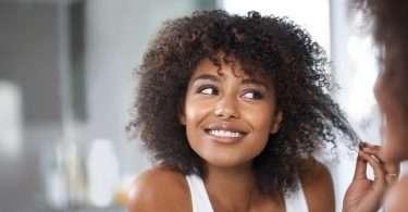 Model mit lockigem Haar sieht sich ihre Haare genau im Spiegel an.