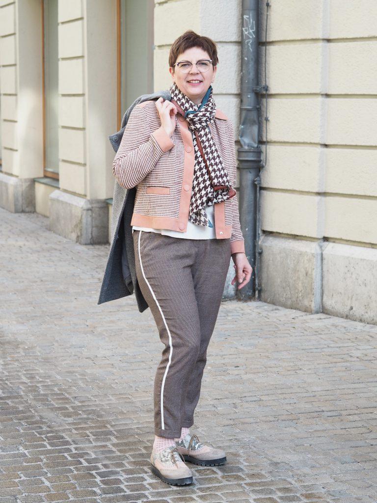 Stilheldin Regina in einem Businessoutfit in Erd- und Rosatönen mit einem dünnen Galonstreifen