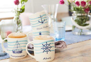 Tassenküchlein in maritimen Tassen auf einem gedeckten Tisch