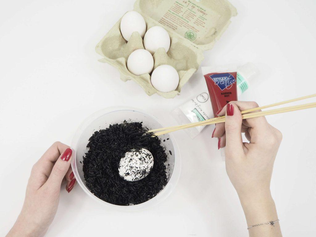 Gefärbter Reis in einer Schale vor einem Eierkarton