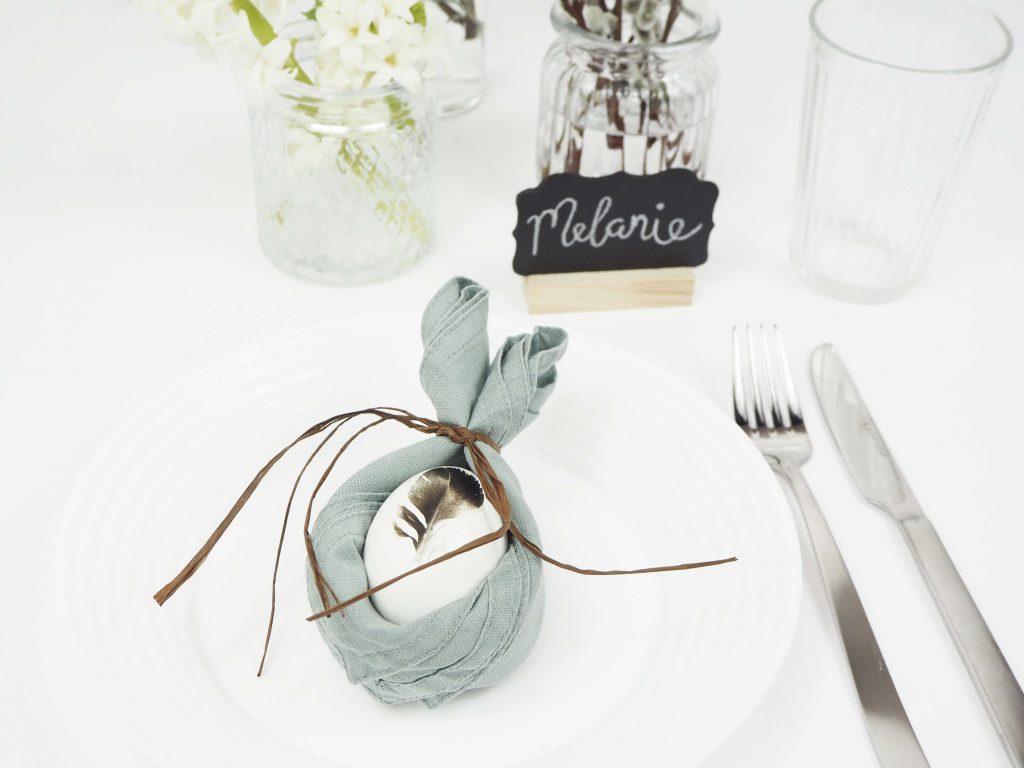Gedeckter Tisch mit einem Teller, auf dem ein Ei umhüllt von einer Serviette liegt