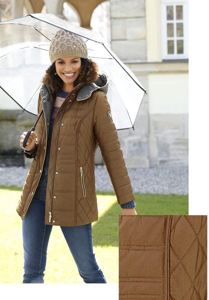 Frau im Herbst Outfit mit Steppjacke, Jeans, Mütze und Regenschirm