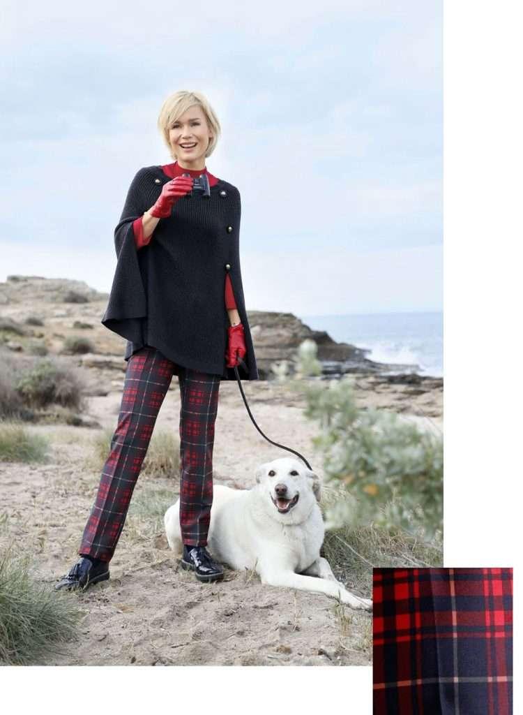 Frau mit Outfit in Rot und Blau mit Hund am Strand