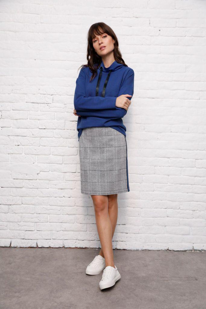 Frau mit grauen Glencheck-Rock, blauem Pulli und Sneakern