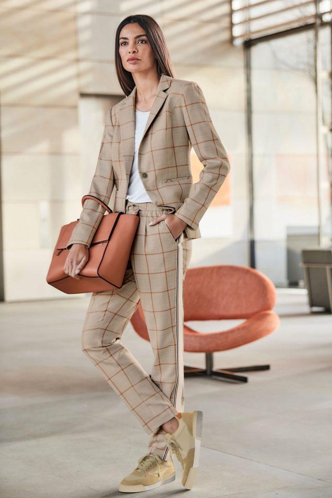 Frau im Büro-Outfit mit Hosenanzug im Glencheck-Muster, Tasche und Sneakern