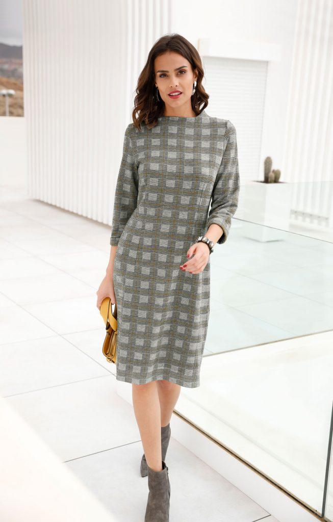 Frau mit Glencheck-Kleid in Grau, grauen Stiefeletten und Handtasche