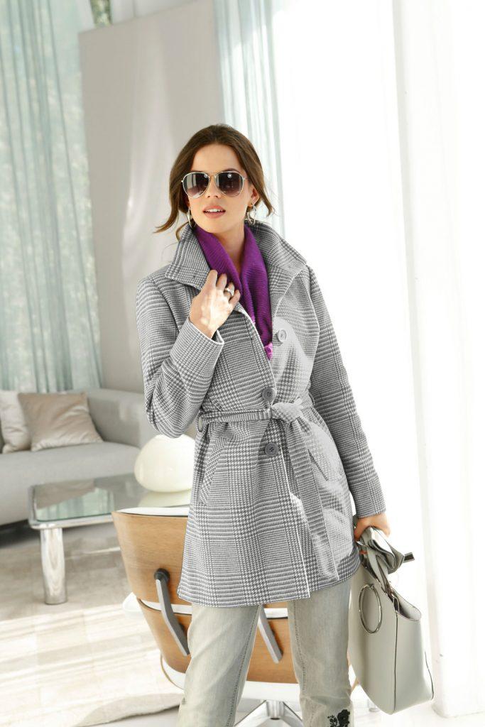 Frau mit Glencheck-Mantel in Grau, lila Pulli, grauer Hose und grauer Tasche